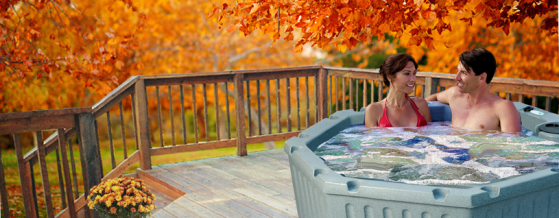 Couple enjoying hot tub in fall leaves