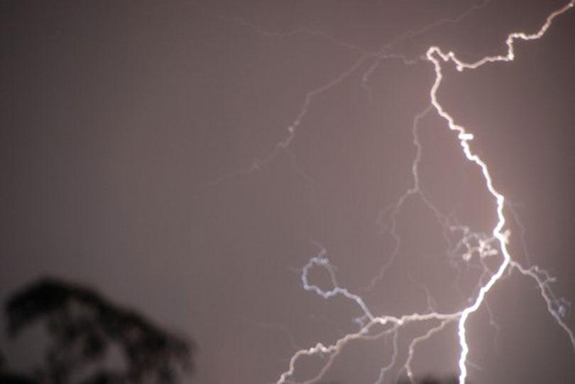 Lightning bolts light up the night sky.