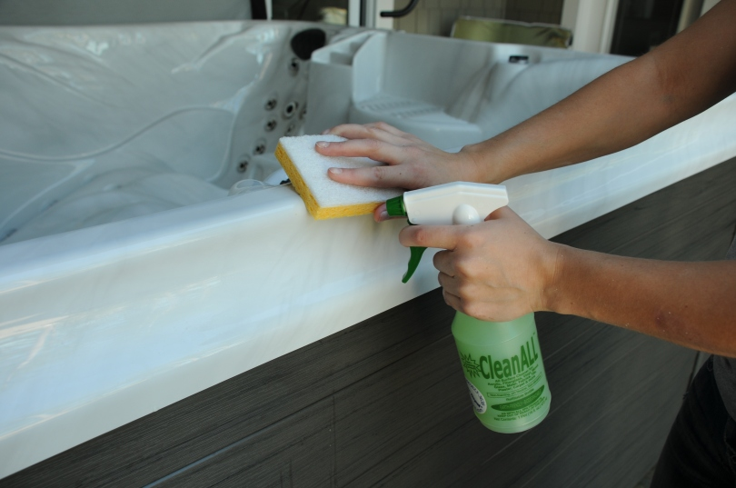 wiping spa shell with sponge and clean all spray