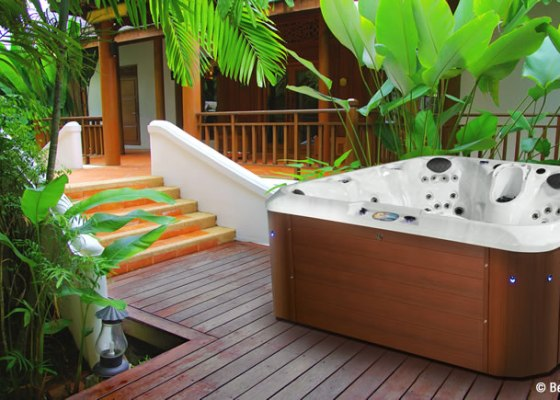 hot tub on deck with tropical plants