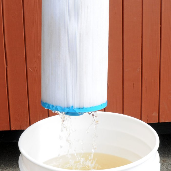 perfectly clean filter being withdrawn from bucket after being soaked with power soak solution