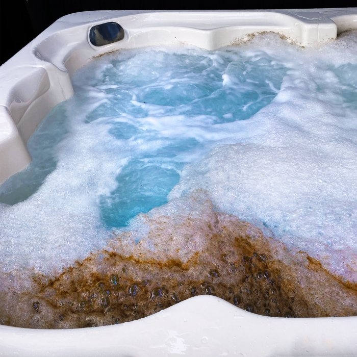 White hot tub with scummy biofilm floating on top of the water